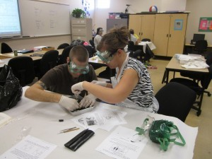 Adult high school students conducting science experiment