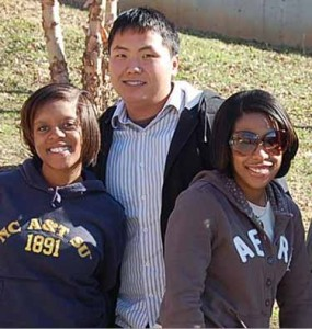Three students posing for picture on campus