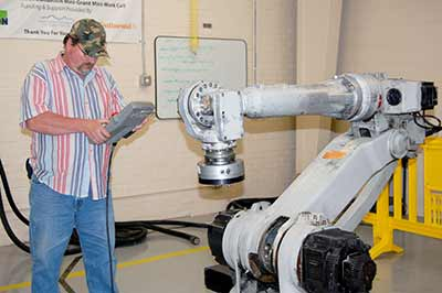Student works with large robotic arm