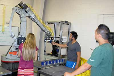Students working with pneumatic arm