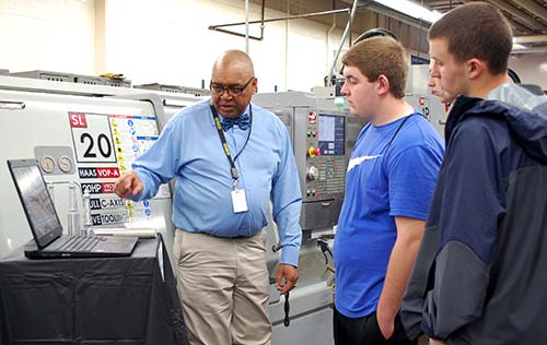A WPCC Instructor discusses a milling machine with students