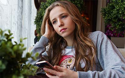 Photo of teen staring into the distance holding a smartphone looking pensive