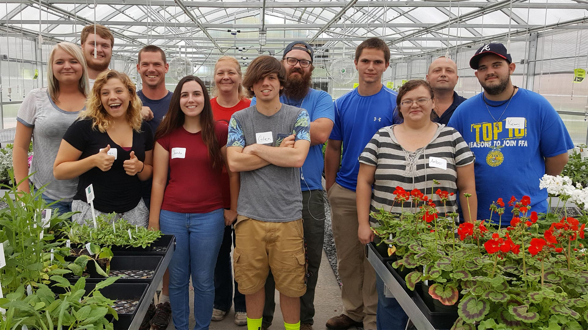 A group of students pose in a greenhouse with plants