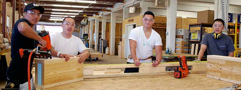 Photo of 4 WPCC Carpentry students working on a wall of a prefabricated building