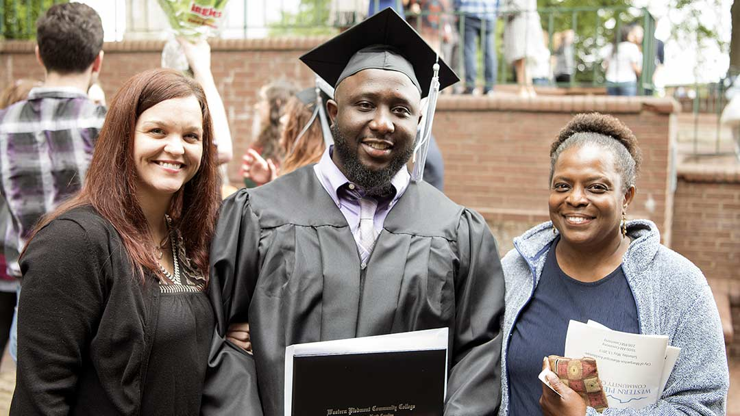 Photo of a WPCC graduate holding his diploma with family and friends