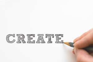 Photo of a hand completing a drawing of the word create