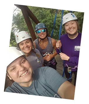 Photo of 4 smiling recreational therapy students at the WPCC ropes course