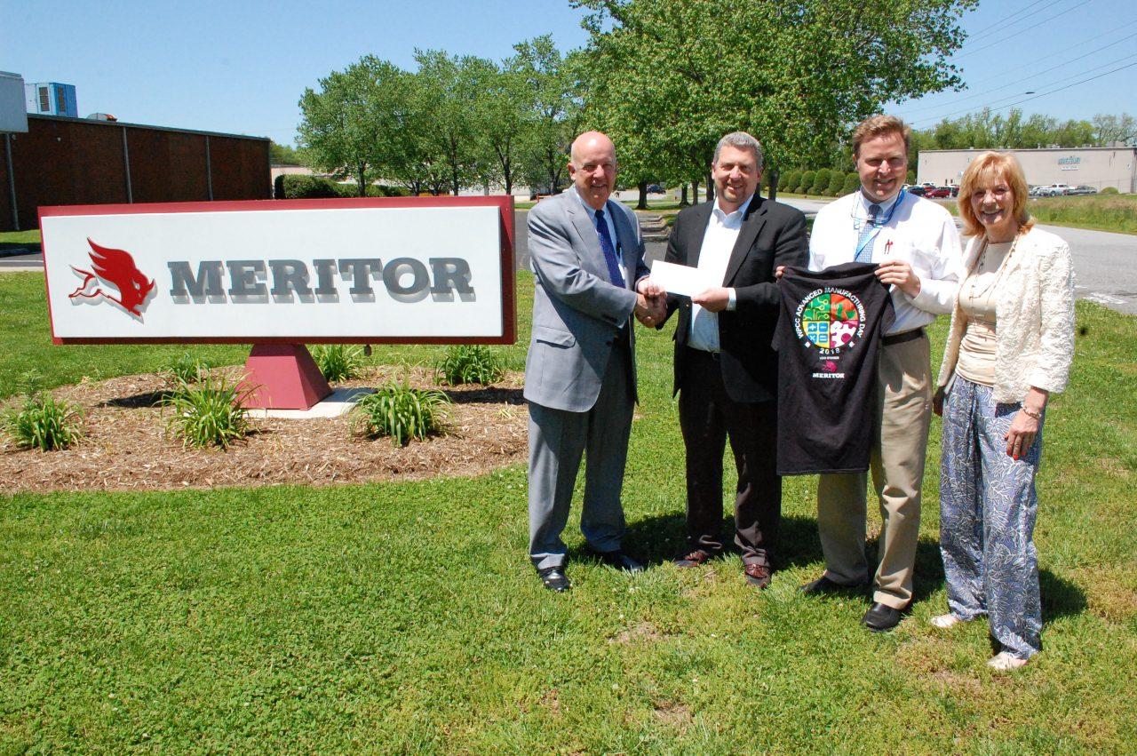 Photo of check presentation with Meritor company sign in the background.