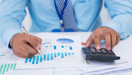 Photo of a man using a calculator and financial charts and spreadsheets