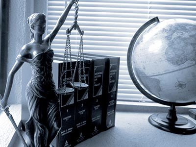 Photo of a legal scales statue, law books, and a globe that represent the paralegal profession