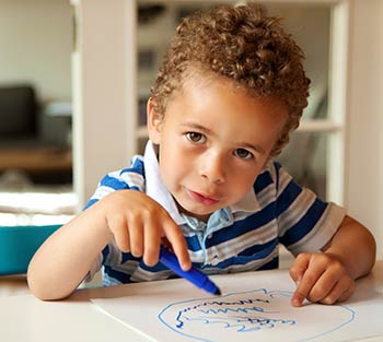 Photo of a toddler boy using a blue marker to work on a drawing he is making at a table