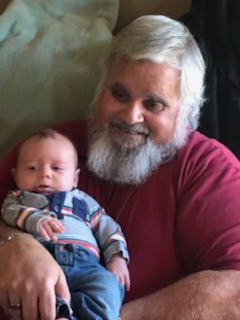 Photo of Harry Carpenter holding a baby