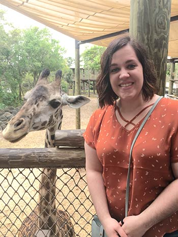 Photo of Laura Davidson at a zoo with a baby giraffe