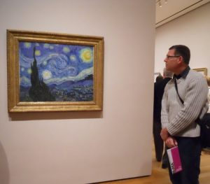 Photo of Mark Poteat looking at a painting in a museum