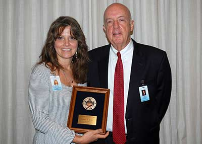 Dr. Michael S. Helmick presents the 2018 Staff Member of the Year Award to Deanna Keller