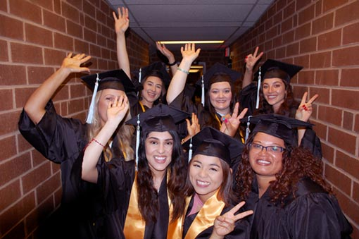 Photo of happy graduates high-fiving and celebrating during the 10 AM Ceremony