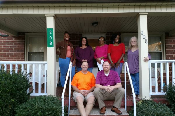 Group of men and women sitting on porch steps posing for a picture