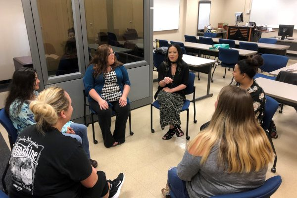 students sitting in a circle practicing group therapy
