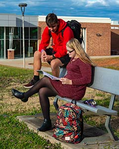 Two WPCC students sit on a bench on the campus grassy commons, talking and studying