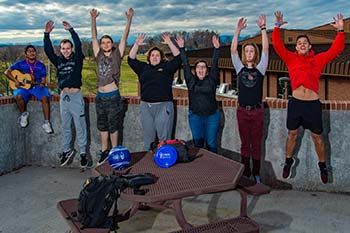 Photo of WPCC students jumping with arms up, excited about being on campus