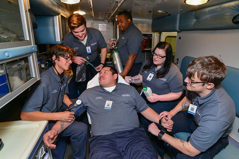Photo of WPCC Emergency Medical TechniciaN Students posing in the training ambulance