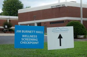 Photo of signs pointing to Jim Burnett Hall, one of the wellness checkpoints on the WPCC campus