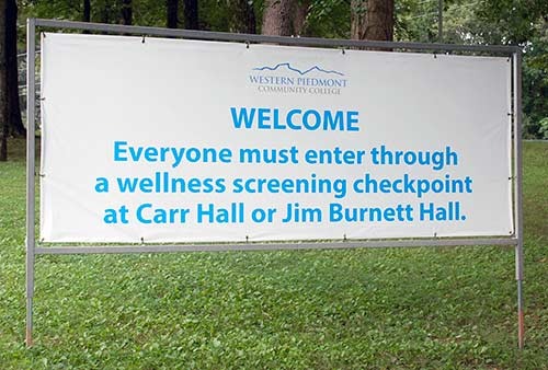 WPCC welcome sign with the reminder that everyone must enter through a wellness screening checkpoint at Carr Hall or Jim Burnett Hall
