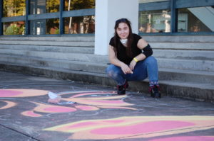 WPCC student Hannah Surby chalks an art piece outside of Moore Hall.