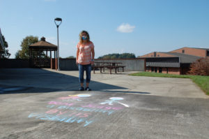 """WPCC student Jessica Davis chalks """"Don't judge a disability by its visibility"""" on campus."""