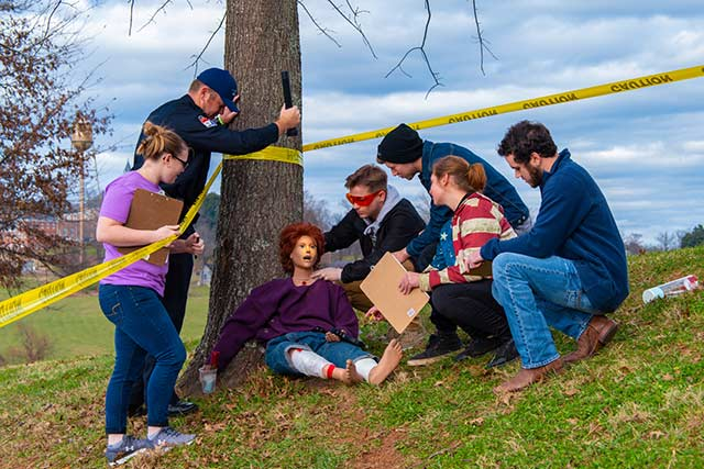 A Wpcc criminal justice class works at a set up murder scene outdoors