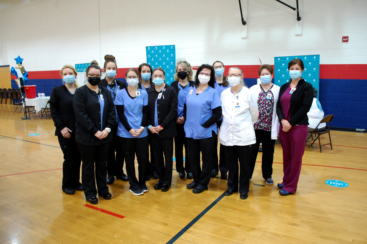 Nursing students and instructors pose in the Freedom High School vaccine clinic, wearing scrubs and masks.