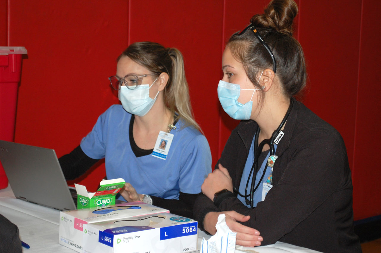 Two nursing students in scrubs and masks look at a laptop at the clinic site.