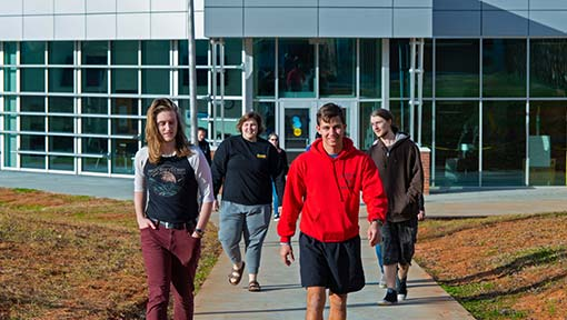 A group of WPCC students are walking on the sidewalk in front of the M Building on the WPCC Main Campus