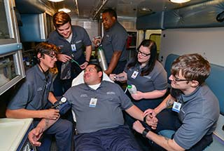 Photo of a group of Emergency Medical Technician students posing inside the back of the WPCC ambulance