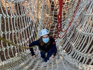 Kim climbing on a rope bridge, wearing a helmet and mask.