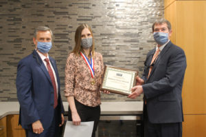 Joel Welch and Scott Mulwee present Kim Edwards with certificate.