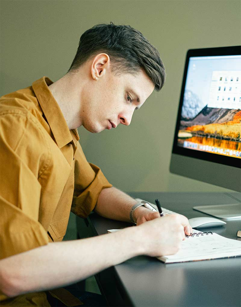 A male student takes notes while sitting at a computer