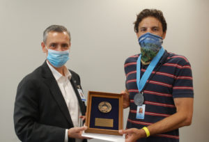 Joel Welch and Robert Vasile in masks holding the award between them.