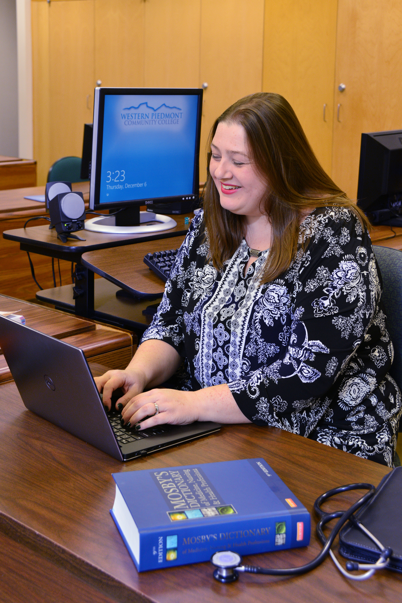 Student working at a computer with medical terms glossary nearby.