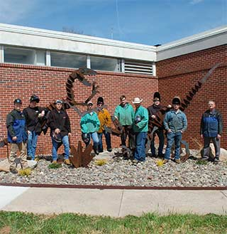 WPCC welding students pose with the new dinosaur garden they created next to Breeden Hall on the WPCC Main Campus