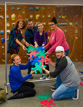 Photo of a group of WPCC recreational therapy students engaging in a class project using large puzzle pieces being passed through a maze
