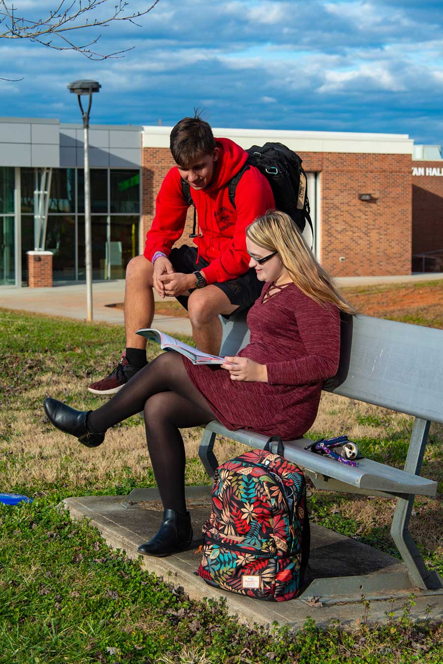 Two WPCC students are studying while sitting on a bench in the grassy commons area in the middle of the WPCC Main Campus