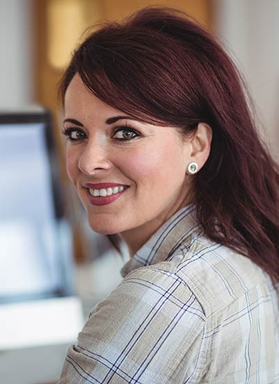 A smiling brunette female student looks back over her shoulder with a computer in the background