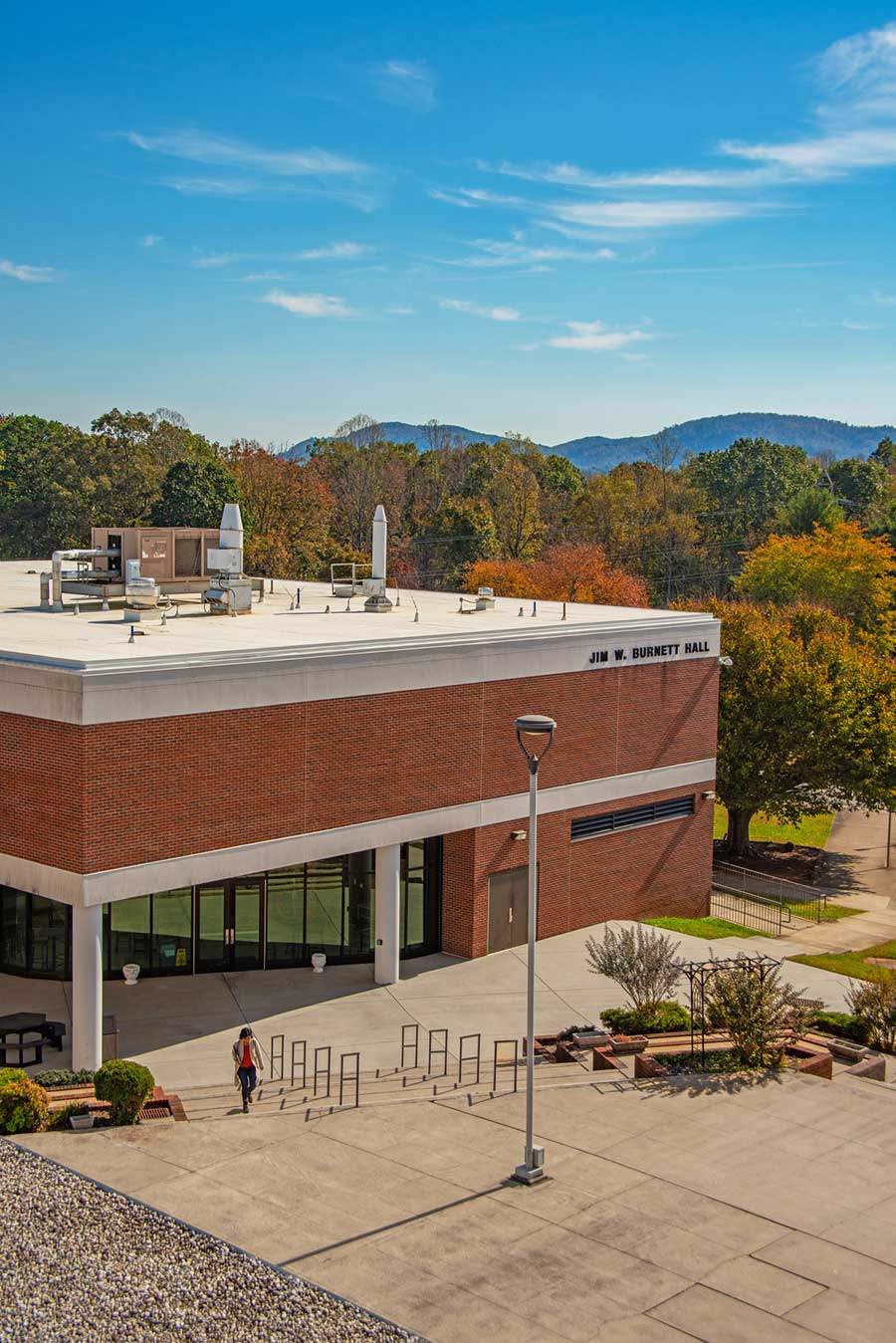 Exterior of Jim Burnett Hall in the fall with beautiful yellow and red leaves on trees in the background on the WPCC Main Campus