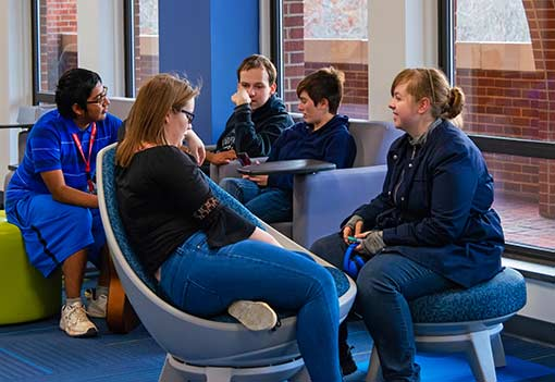 A group of students chat in a common area in the WPCC Library