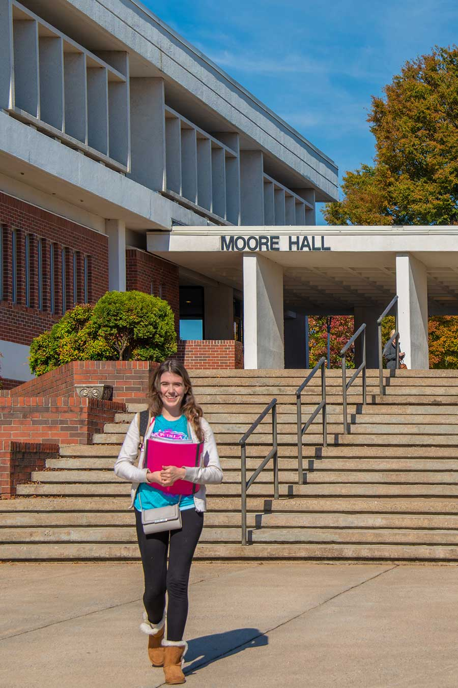 A female WPCC student walks past Moore Hall