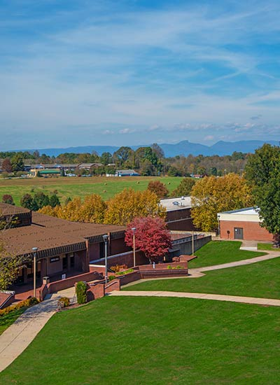 A view of the grassy commons on the WPCC main campus in fall with Table Rock and Hawksbill Mountains in the background