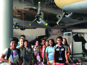 Students standing underneath airplanes at the WWII Museum in New Orleans.